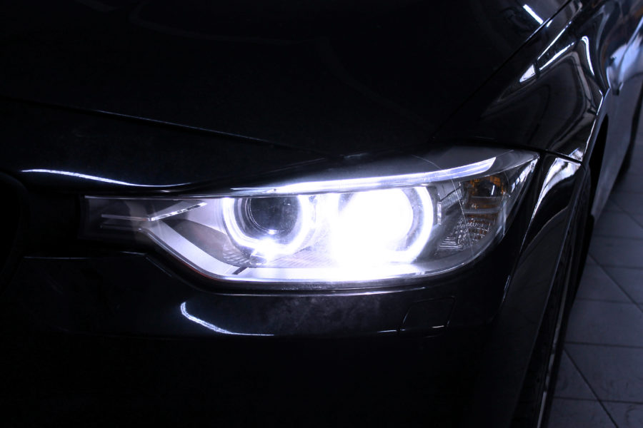 Macro view of headlight detail of modern automobile with auto projector lens. Front view of vehicle head xenon lamp. Concept of car detailing, light and LED technology close up background