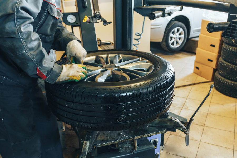 Mechanic worker makes computer wheel balancing on special equipment machine tool in auto repair service, toned photo