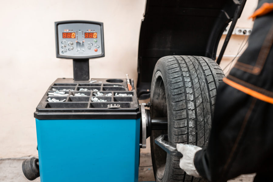 excellent balancing Wheel on zero. Technician spins a car wheel. The tool for repair - Lead small weights and pincers for Wheel Balancing. Car service.